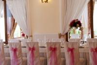 Kokardy na krzesłach w kolorze dekoracji na sali weselnej.